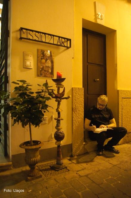 Jaime Roig de Diego escribiendo una dedicatoria en un portal de la calle Missió al lado de la Galería Missió21Art, donde se celbró su Exposición coloquio.